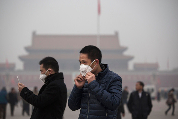 """BEIJING, CHINA - DECEMBER 09: A tourist puts on a face mask to protect against pollution as he visits Tiananmen Square during smog in Tiananmen Square on December 9, 2015 in Beijing, China. The Beijing government issued a """"red alert"""" Sunday for the first time since new standards were introduced earlier this year as the city and many parts of northern China were shrouded in heavy pollution. Levels of PM 2.5, considered the most hazardous, crossed 400 units in Beijing, lower then last week, but still nearly 20 times the acceptable standard set by the World Health Organization. The governments of more than 190 countries are meeting in Paris to set targets on reducing carbon emissions in an attempt to forge a new global agreement on climate change. (Photo by Kevin Frayer/Getty Images)"""